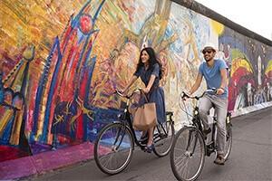 Una pareja pasea en bici por el Muro de Berlín. Autor: Turismo de Alemania.