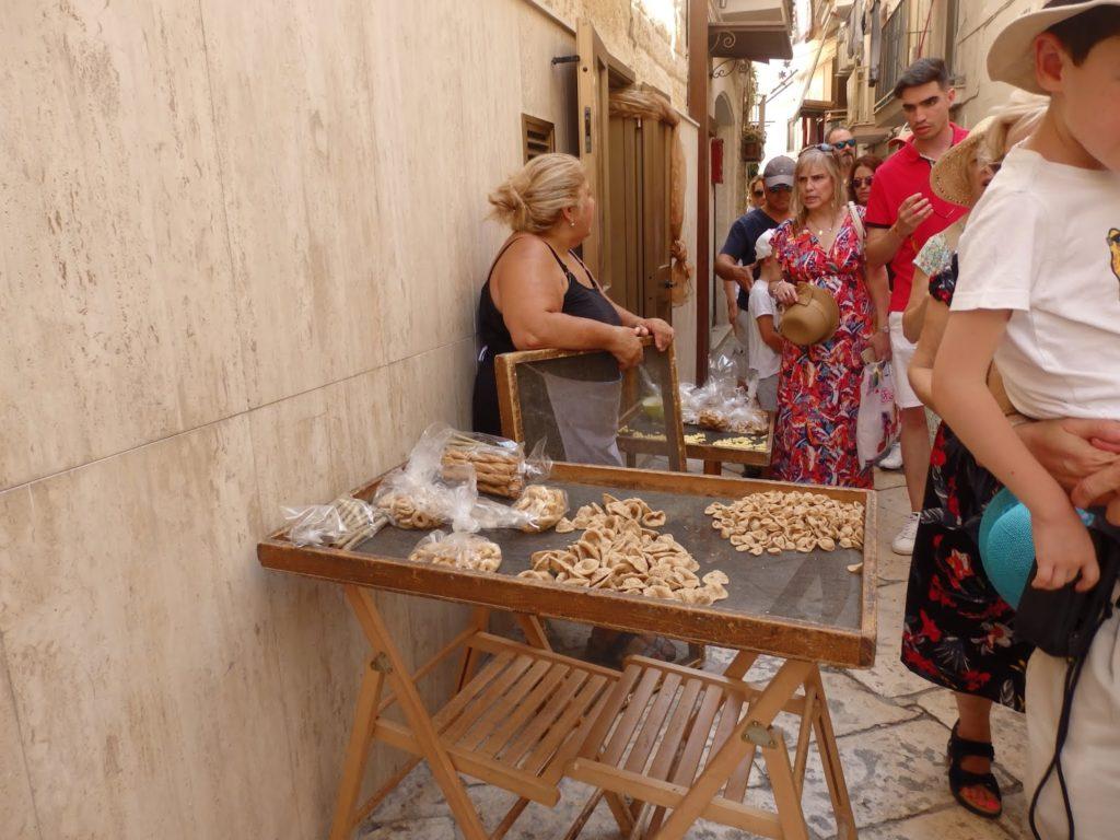 Una mujer vende pasta en la calle en Bari (Italia)